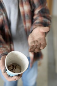 Hands of Homeless Man with Change in Cup